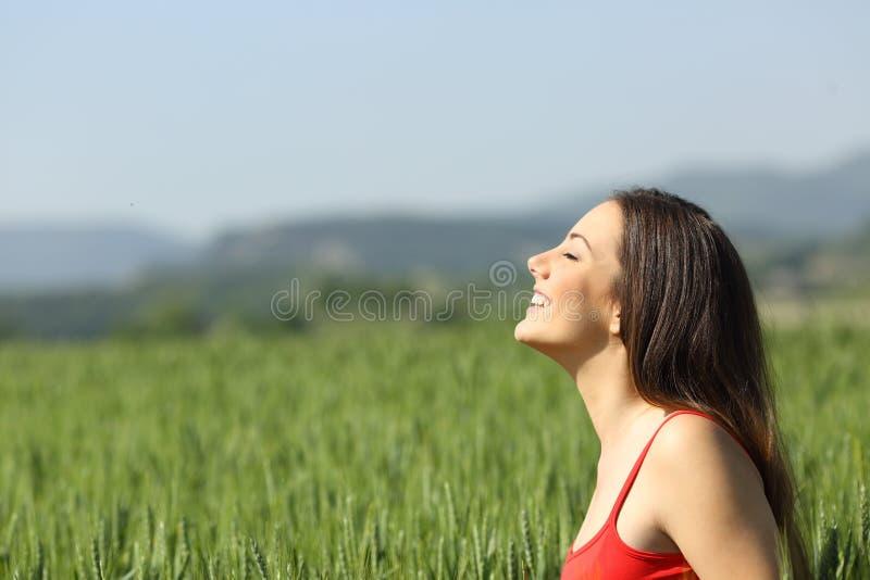 Mujer feliz en aire fresco de respiración rojo en un campo imagenes de archivo