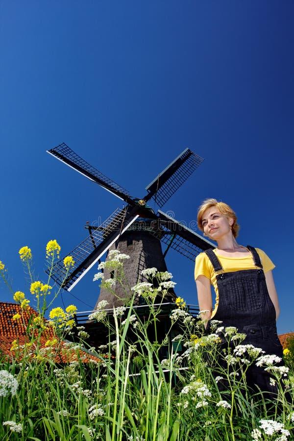 Mujer feliz en aldea con el molino de viento fotografía de archivo
