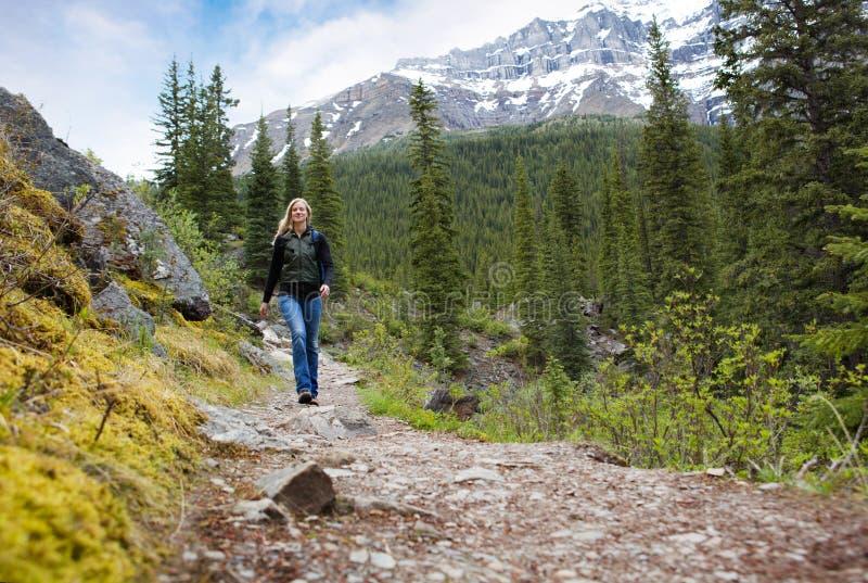 Mujer feliz en alza de la montaña imagenes de archivo