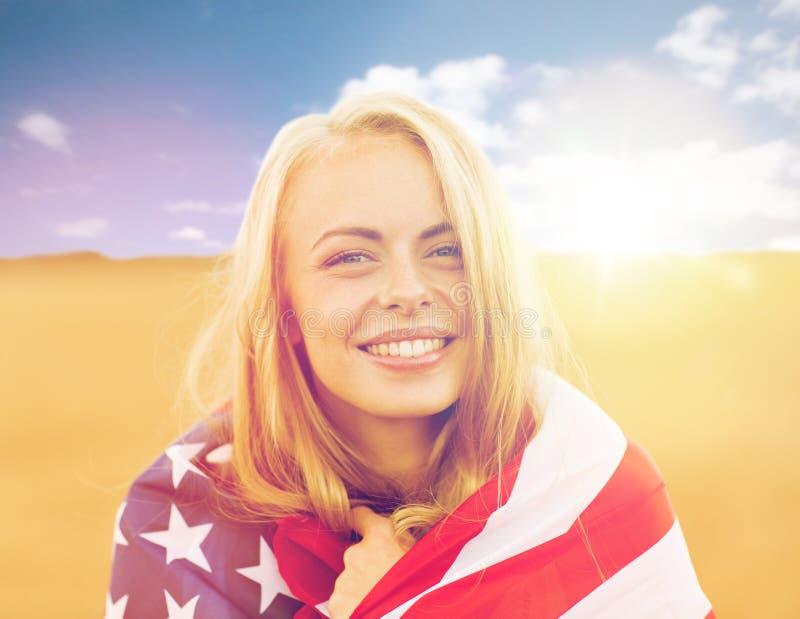 Mujer feliz en bandera americana en campo de cereal fotos de archivo libres de regalías