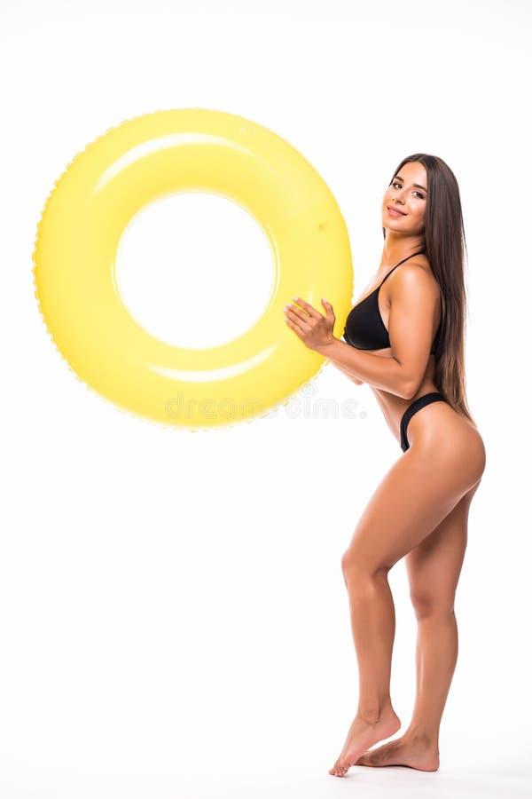 Mujer feliz en bikinin con el anillo anaranjado de la nadada aislado en el fondo blanco foto de archivo