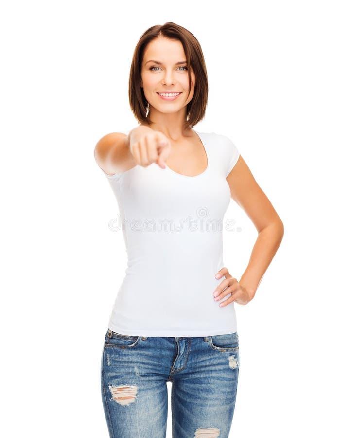 Mujer feliz en camiseta blanca en blanco que señala en usted foto de archivo