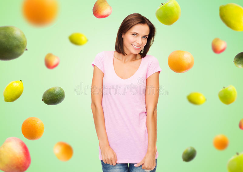 Mujer feliz en camiseta blanca en blanco sobre las frutas imagen de archivo libre de regalías