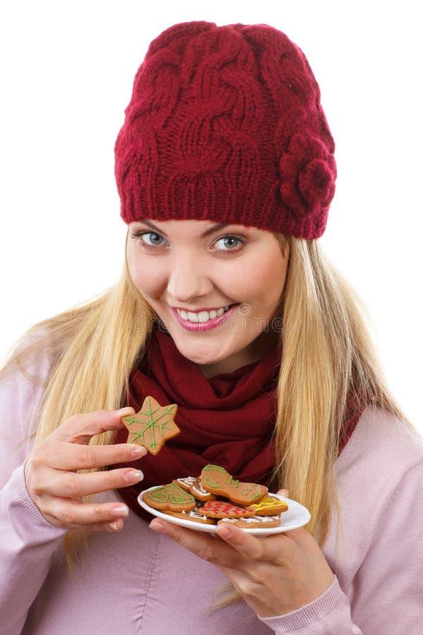 Mujer feliz en casquillo y mantón de lana que come las galletas del pan de jengibre, fondo blanco, tiempo de la Navidad fotos de archivo
