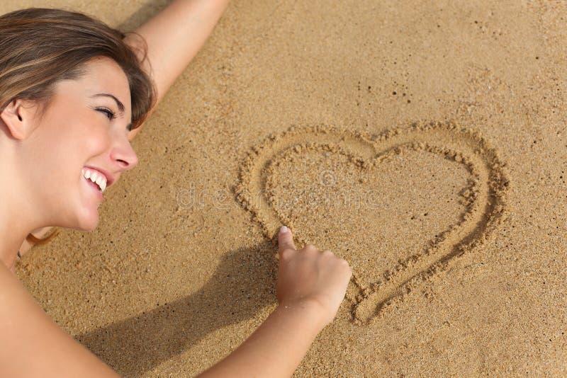 Mujer feliz en el amor que dibuja un corazón en la arena de la playa imagenes de archivo