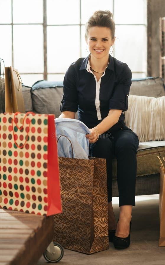 Mujer feliz en el apartamento del desván que comprueba nuevos purchasings imagen de archivo libre de regalías