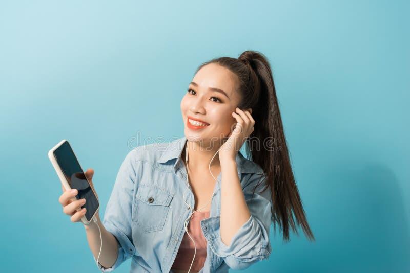 Mujer feliz en el baile de la ropa informal y el escuchar la música con placer vía los auriculares sobre fondo azul foto de archivo libre de regalías