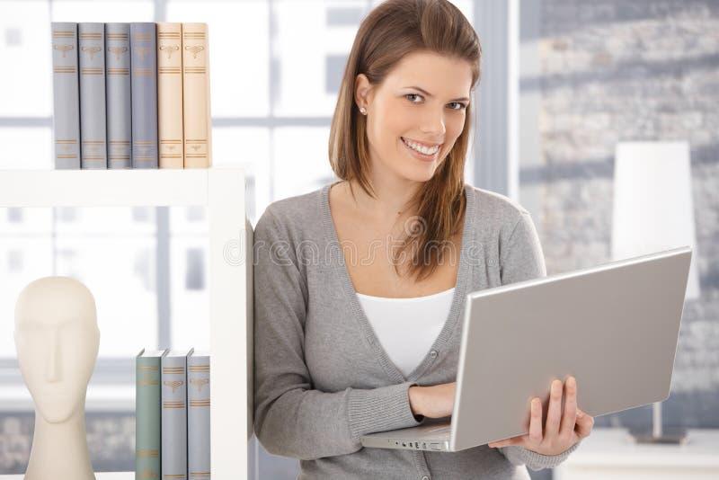Mujer feliz en el estante para libros con el ordenador
