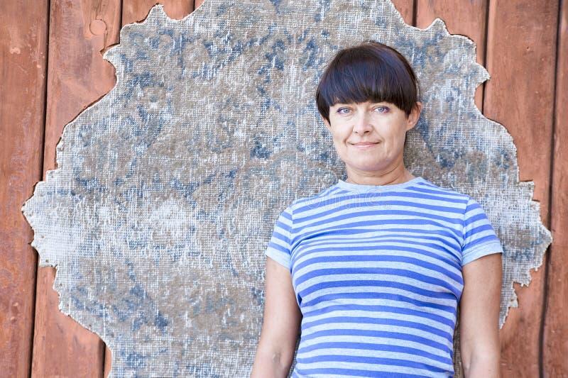 Mujer feliz en el fondo de una pared de madera fotografía de archivo