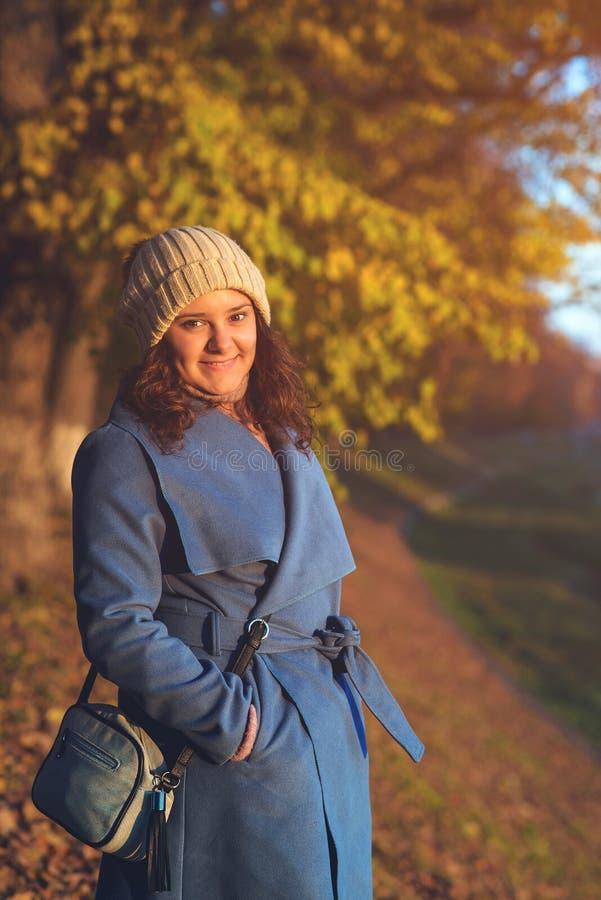 Mujer feliz en el parque del otoño El clima cálido y soleado Niña disfrutando de la caminata del otoño Moda de otoño femenina imagenes de archivo