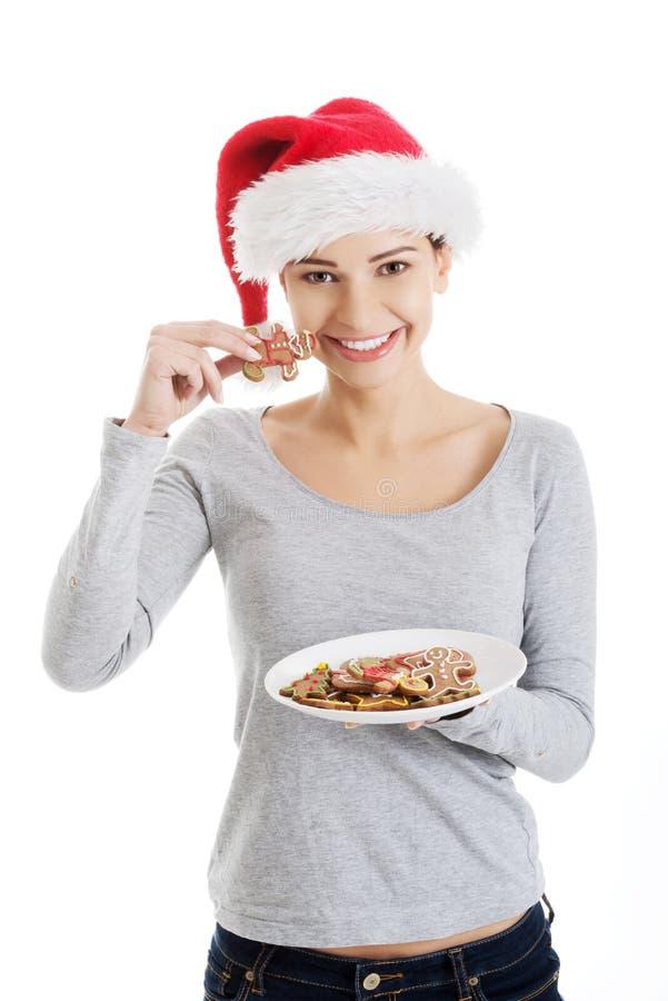 Mujer feliz en el sombrero de santa que come las galletas de la Navidad fotografía de archivo libre de regalías