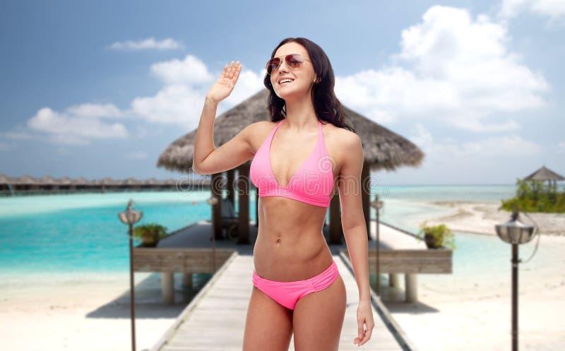 Mujer feliz en gafas de sol y bikini en la playa fotografía de archivo