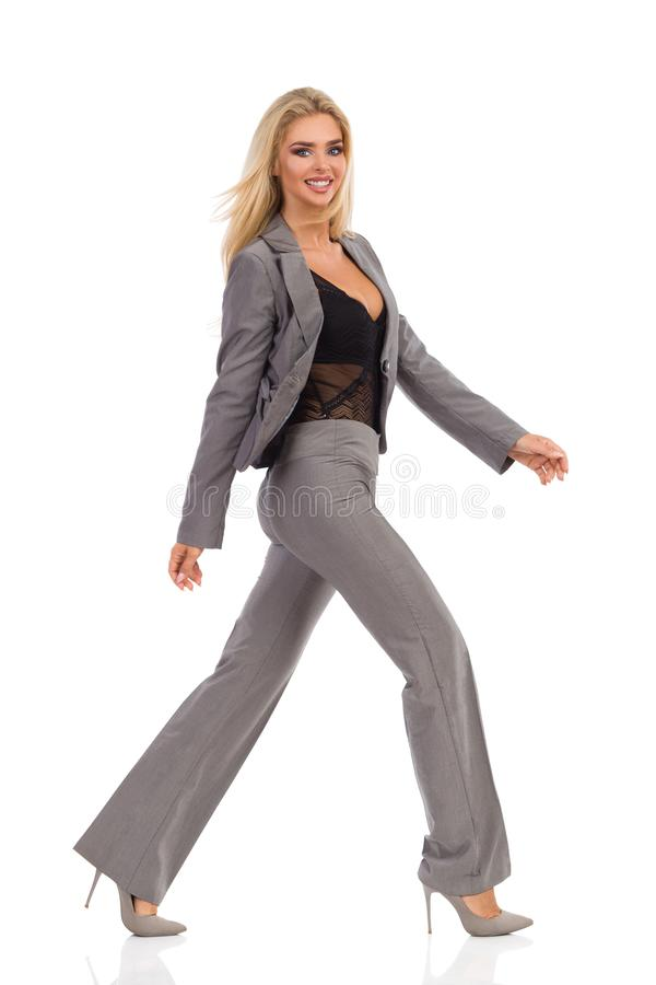 Mujer feliz en Gray Suit Is Walking And que mira la cámara imagen de archivo
