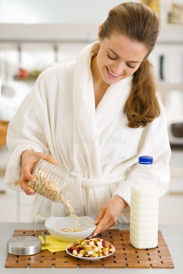 Mujer feliz en la albornoz que pone la harina de avena en la placa imagen de archivo