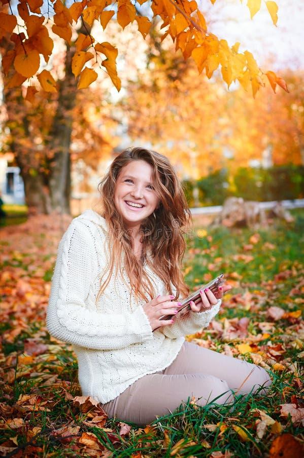 Mujer feliz en la blusa blanca que se sienta en la hierba en parque del otoño imágenes de archivo libres de regalías