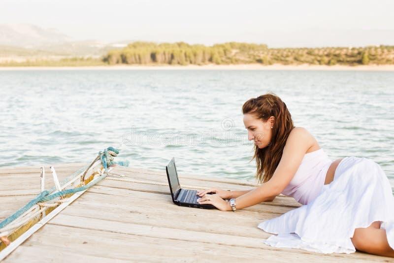 Mujer feliz en la computadora portátil fotos de archivo libres de regalías