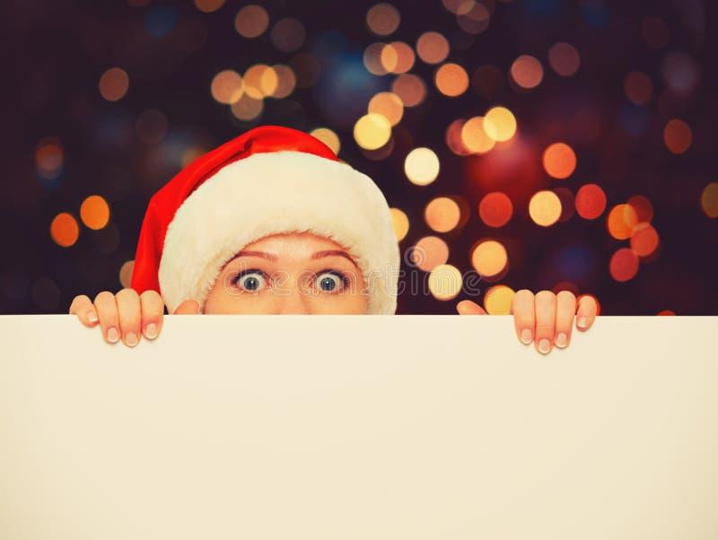 Mujer feliz en la Navidad con el cartel blanco vacío en blanco imagen de archivo libre de regalías