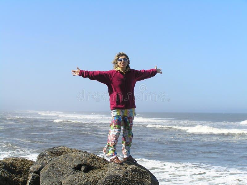 Mujer feliz en la orilla del océano imagenes de archivo