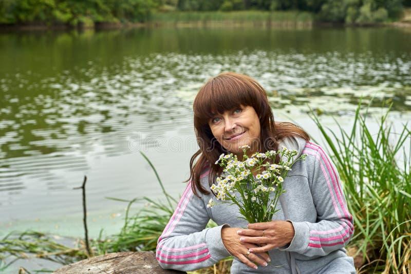 Mujer feliz en la orilla del río fotografía de archivo