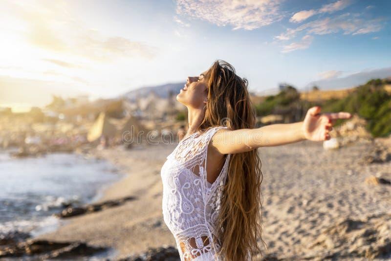 Mujer feliz en la playa durante vacaciones de los días de fiesta del viaje foto de archivo libre de regalías