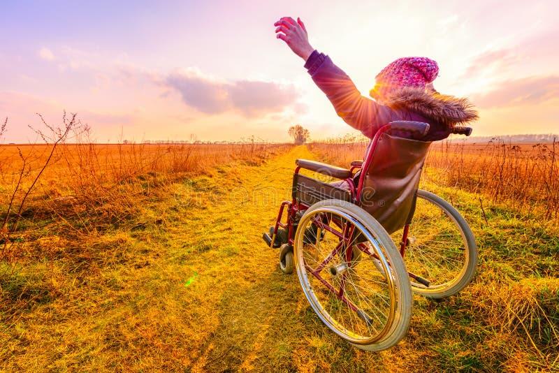 Mujer feliz en la puesta del sol Una chica joven en una silla de ruedas fotografía de archivo libre de regalías