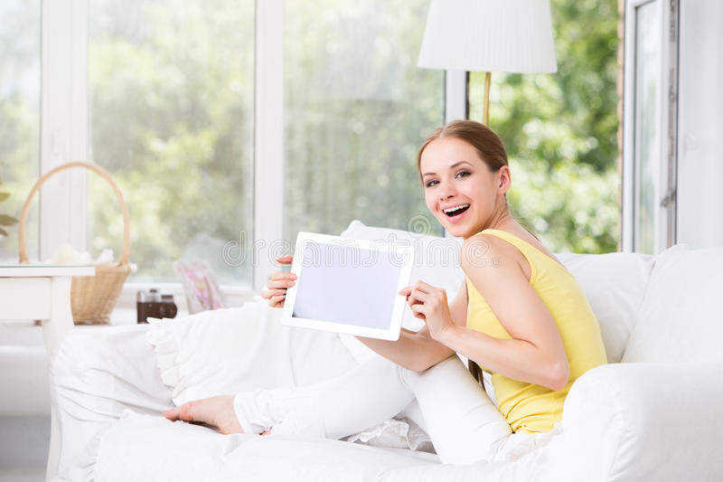 Mujer feliz en la sala de estar que muestra una tableta electrónica imágenes de archivo libres de regalías