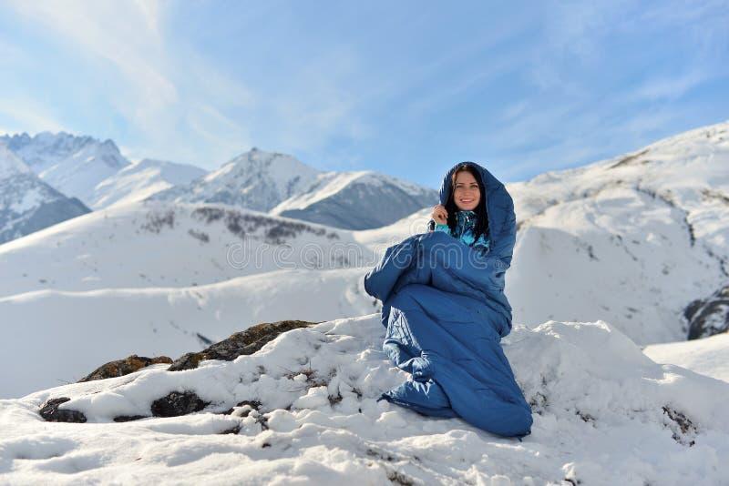 Mujer feliz en saco de dormir en montañas nevosas imagenes de archivo
