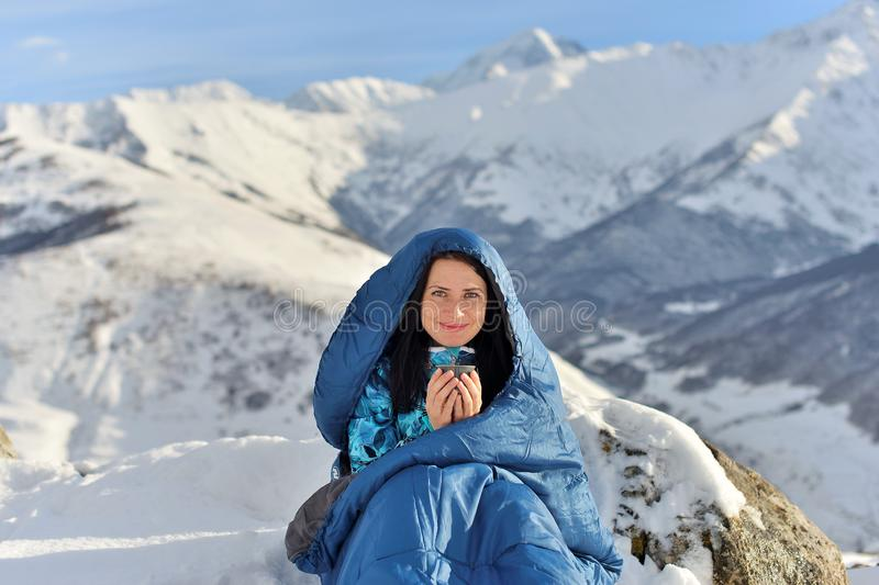 Mujer feliz en saco de dormir en montañas nevosas imagen de archivo libre de regalías