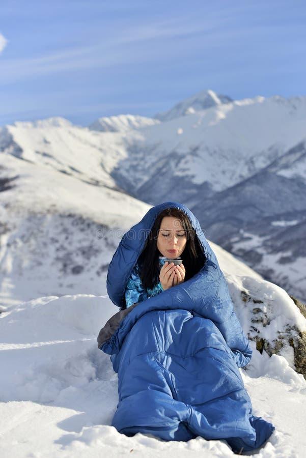 Mujer feliz en saco de dormir en montañas nevosas imágenes de archivo libres de regalías