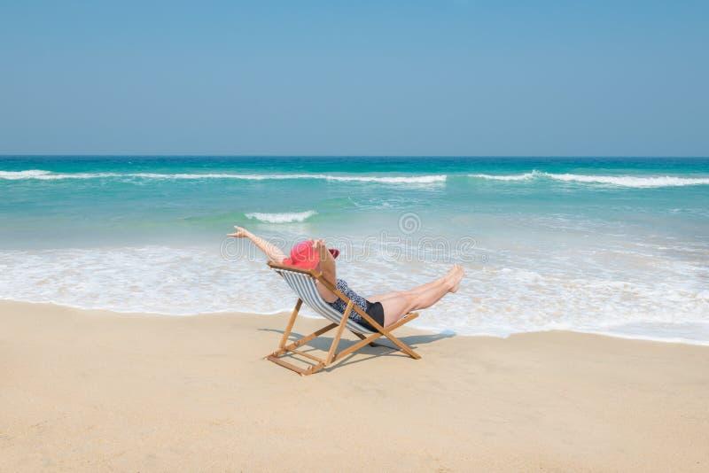 Mujer feliz en sunhat rojo en la playa foto de archivo