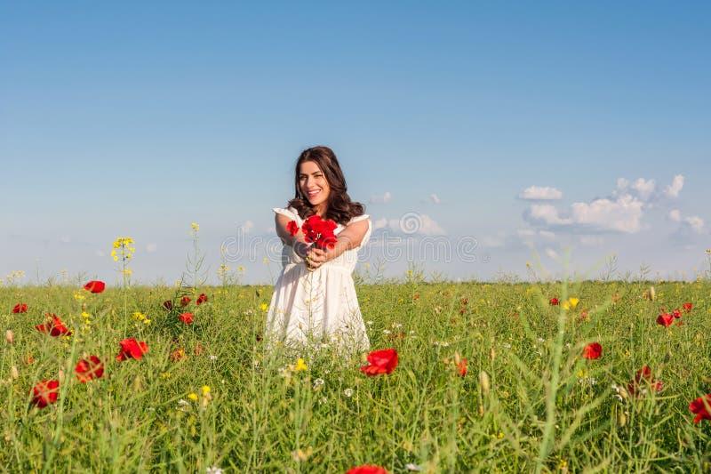 Mujer feliz en un campo floreciente de la amapola al aire libre con un ramo de las amapolas foto de archivo libre de regalías