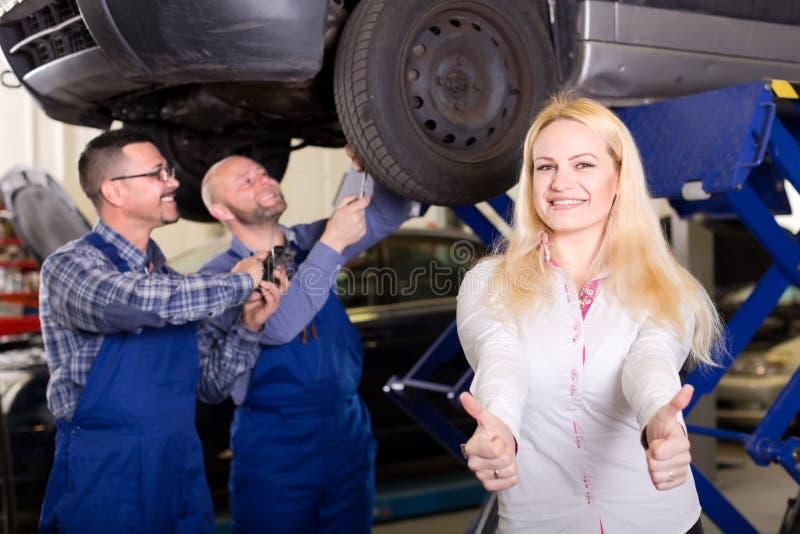 Mujer feliz en un taller de reparaciones del coche imagen de archivo