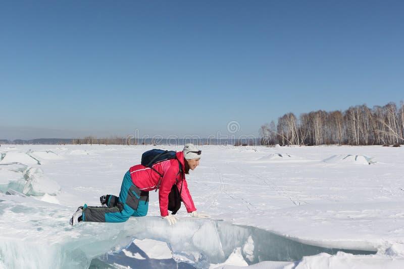 Mujer feliz en una chaqueta roja que se arrastra en una masa de hielo flotante de hielo en un río fotografía de archivo libre de regalías