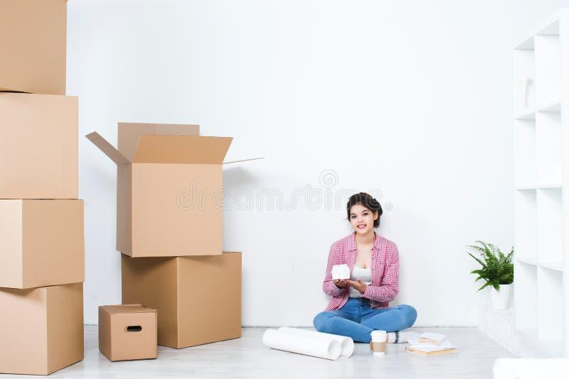 Mujer feliz en una nueva casa Piense hacia fuera el interior foto de archivo