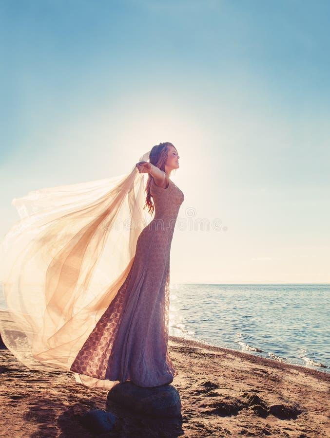 Mujer feliz en vestido hermoso durante Sun foto de archivo libre de regalías