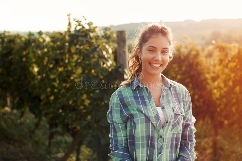 Mujer feliz en viñedo que comprueba las uvas foto de archivo libre de regalías