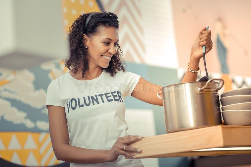 Mujer feliz encantada que cocina en la cocina imagenes de archivo