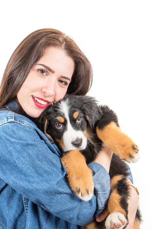 Mujer feliz enorme un perrito del perro de montaña bernese imágenes de archivo libres de regalías