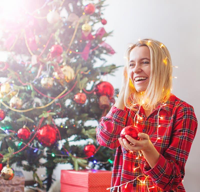 Mujer feliz envuelta en luces de la Navidad fotos de archivo
