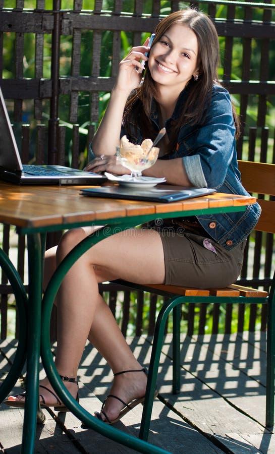 Mujer feliz hermosa con el teléfono móvil en café foto de archivo