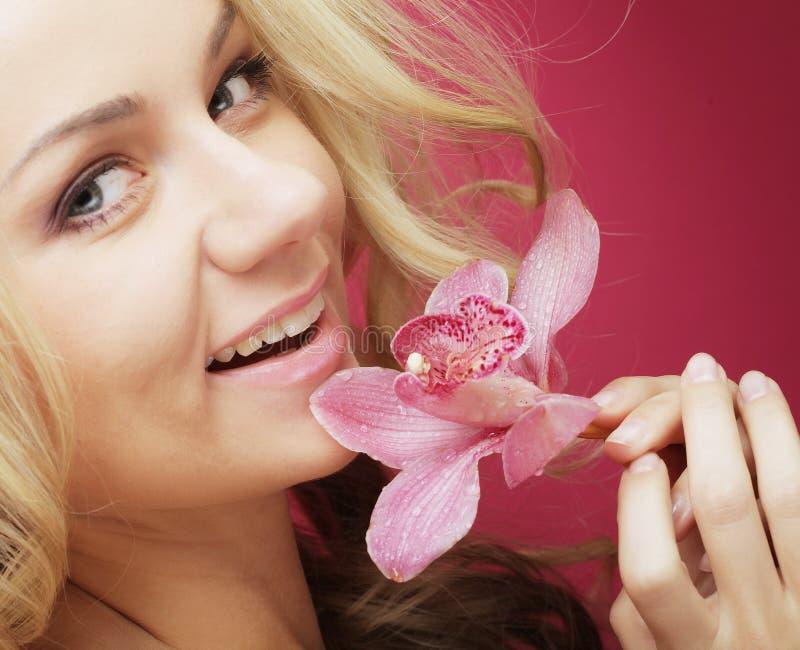 Mujer feliz hermosa con la flor de la orquídea fotografía de archivo libre de regalías
