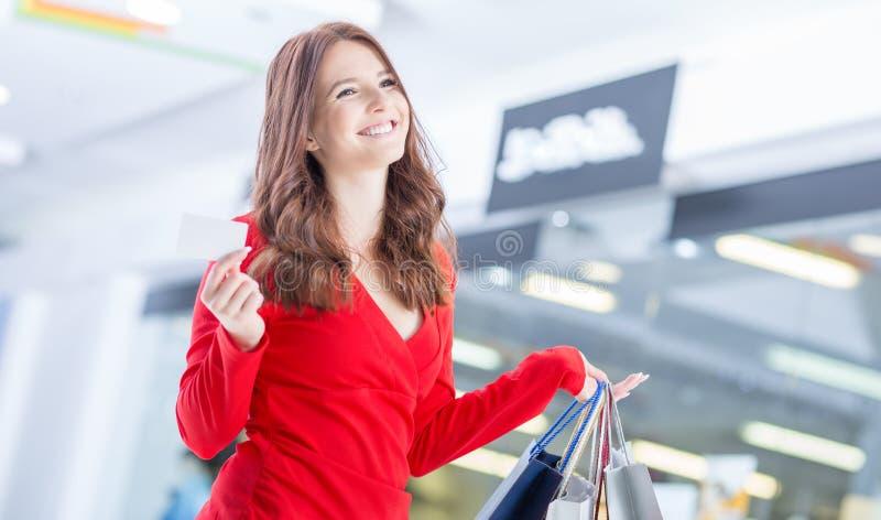 Mujer feliz hermosa con la tarjeta de cr?dito y bolsos de compras en centro comercial fotos de archivo