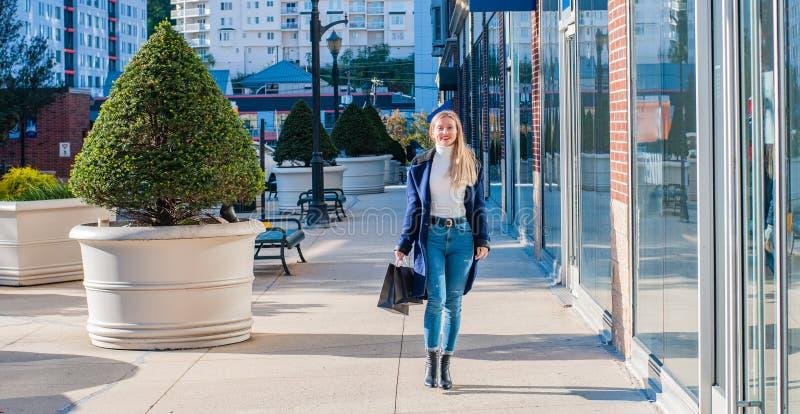 Mujer feliz hermosa con los bolsos de compras que camina en la alameda imagen de archivo