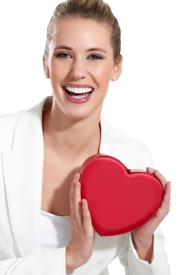 Mujer feliz hermosa con un corazón imagen de archivo
