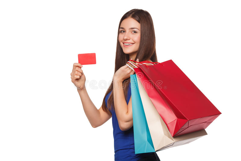 Mujer feliz hermosa de la sonrisa que sostiene los panieres y que muestra la tarjeta del crédito en blanco, venta, aislada en el  imagen de archivo libre de regalías