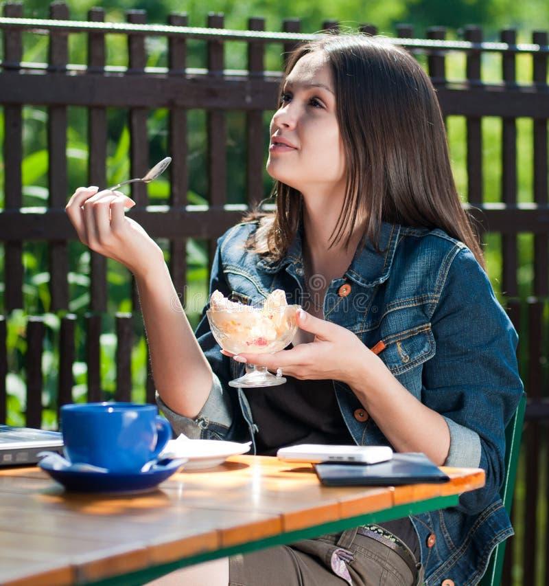 Mujer feliz hermosa en café que come el helado imagenes de archivo
