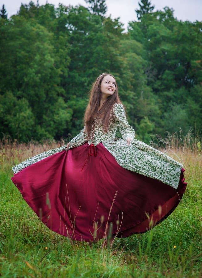 Mujer feliz hermosa en el baile medieval largo del vestido foto de archivo libre de regalías