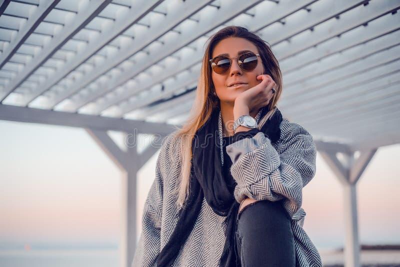 Mujer feliz hermosa en las gafas de sol que se colocan en el mar, muchacha en capa gris imágenes de archivo libres de regalías