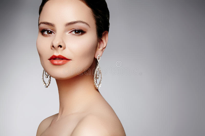 Mujer feliz hermosa en pendientes de lujo de la moda Joyería brillante del diamante con los brilliants Retrato retro atractivo de fotografía de archivo libre de regalías