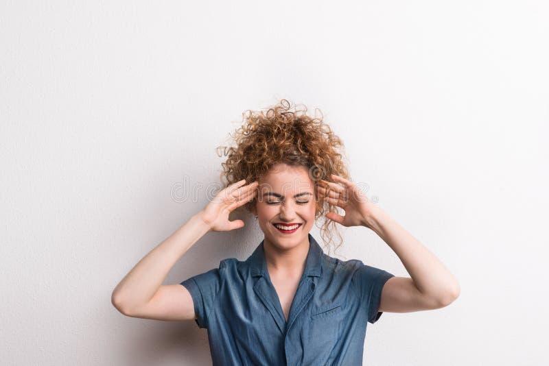 Mujer feliz hermosa joven en el estudio, manos en los templos fotos de archivo